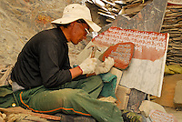 Stone-carver inscribes prayer, or mani, stones with sutras, most often the mantra of Chenresig, the Bodhisattva of Compassion, Om Mani Padme Hum at the foot of Chagpo Ri, the hill opposite the Potala Palace, for sale to pilgrims, Lhasa, Tibet, China.