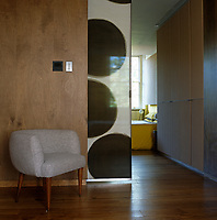 An abstract sliding screen by Florence Dufieux separates the bedroom and bathroom