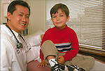 portrait of smiling Asian doctor with young boy sitting on examination table