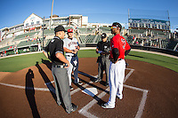James Baldwin (right) meets with Hickory Crawdads coach Chad Comer (16) and umpires Reid Joyner (left) and Cody Clark prior to their South Atlantic League game at CMC-Northeast Stadium on May 22, 2015 in Kannapolis, North Carolina.  The Intimidators defeated the Crawdads 4-3.  (Brian Westerholt/Four Seam Images)