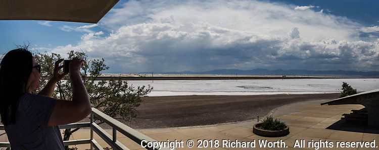 From an observation platform along Interstate 80 in Utah, just east of the Nevada state line, a visitor photographs the gathering storm clouds over the Salt Flats of the Great Salt Lake in a multi-image panoramic.