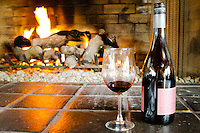 A red wine glass and wine bottle are seen in front of a roaring fire in a fireplace.