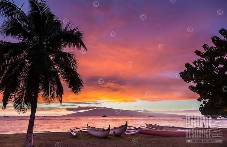 A man strolls the shoreline near outrigger canoes on a Maui beach as the sun sets behind Lana'i.
