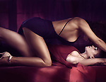 Artistic sensual photo of a sexy lesbian couple making love, two beautiful women in elegant blue and red dresses, one on top of another about to kiss Image © MaximImages, License at https://www.maximimages.com