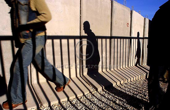 Palestinians walk pass the security wall which separates between the Palestinian neighbor of Abu Dis and Jerusalem, December 12, 2003. Photo by Quique Kierszenbaum