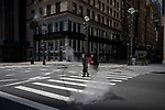 A man and a woman wearing face masks cross Fifth Avenue in an attempt to find a taxi during the coronavirus pandemic in New York, U.S., on Wednesday, April 1, 2020.  Photograph by Michael Nagle