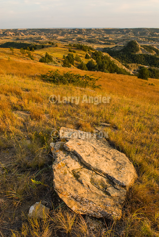 An ancient slab of rock in the rolling hills of the badlands and grasslands with clouds in the late afternoon in Theodore Roosevelt National Park, North Dakota