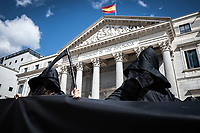 MADRID, SPAIN - MARCH 18: A group of people dressed as the grim reaper protest with a giant banner against the euthanasia law in front of the congress of deputies on 18 march in Madrid, Spain. In 1989 Maria Jose Carrasco was diagnosed with multiple sclerosis, a disease that was degrading her physically to the point of being unable to fend for herself.In 2019, she repeatedly asked to stop living in order to stop suffering, but in part from the institutions did not get any response. With the help of her husband Angel Hernandez in April 2019 she committed suicide. The case raised a lot of excitement at the national level and promoted the current euthanasia law that is approved today on March 18, 2021 in the congress of deputies in the face of much controversy and the conservative parties against, who have protested at the gates of Congress during voting. (Photo by Joan Amengual/VIEWpress)