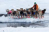 Kelly Maixner walks his dogs across the open water of the Happ RIver in Ptarmigan Valley on the way to Rohn from the Rainy Pass checkpoint during Iditarod 2016.  Alaska.  March 07, 2016.  <br /> <br /> Photo by Jeff Schultz (C) 2016 ALL RIGHTS RESERVED