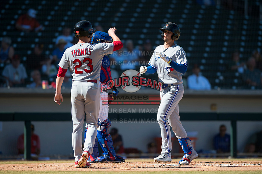 Surprise Saguaros designated hitter Cavan Biggio (26), of the Toronto Blue Jays organization, is congratulated by Lane Thomas (23), of the St. Louis Cardinals organization, after hitting a home run during an Arizona Fall League game against the Mesa Solar Sox at Sloan Park on November 1, 2018 in Mesa, Arizona. Surprise defeated Mesa 5-4 . (Zachary Lucy/Four Seam Images)