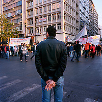A man watching demonstrators as they walk from Omonia towards Syntagma square during the financial crisis.