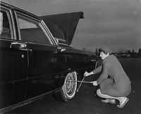 ARCHIVE -<br /> Femmes au Travail 1969 -<br /> conductrice de taxi changeant une roue<br /> <br /> <br /> PHOTO :  AQP -  Photo Moderne