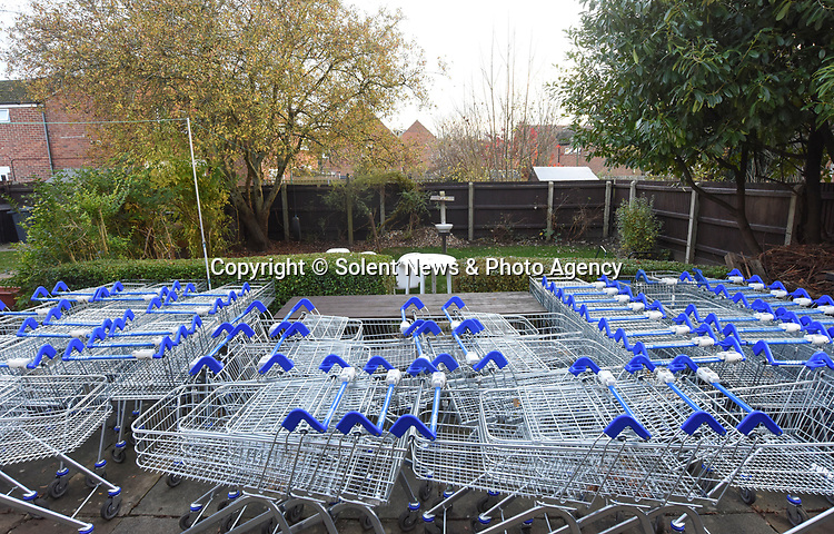 Pictured: The 65 trollies in Bernie Lucker's backgarden in Andover, Hants.<br /> <br /> Former supermarket worker Bernie Lucker has admitted he is off his trolley - after collecting 65 abandoned shopping carts and storing them all on his patio.  The exasperated father of three found 30 of them lying around near his house in just one evening and decided to take them home.<br /> <br /> And in the three weeks since he first started, the 65-year-old has more than doubled his collection, much to his wife's bemusement.  He is now hoping the trollies - which measure 260 feet when lined up - will finally get taken off his hands, after repeatedly contacting Tesco to get them picked up.  SEE OUR COPY FOR MORE DETAILS.<br /> <br /> © Ewan Galvin/Solent News & Photo Agency<br /> UK +44 (0) 2380 458800