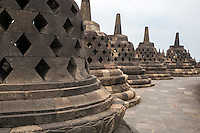 Borobudur, Java, Indonesia.  Stupas on the upper level of the temple.  The diamond-shaped holes symbolize the passions that still linger as men rise toward Nirvana.  On the next higher terrace the holes in the stupas are square, symbolizing  the overcoming of passions as one approaches Nirvana.