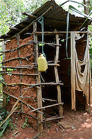 KENYA, Kisumu County, Kaimosi, toilet built from clay, timber and tinshed in village/ KENIA, Toilette aus Lehm, Holz und Wellblech in einem Feld in einem Dorf