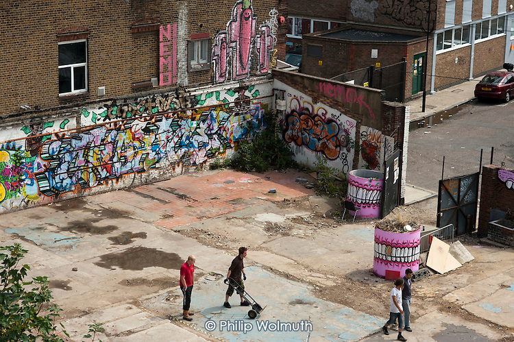 Graffiti and wall art in a yard in Hackney Wick.  The rundown area of warehouses, small industrial units and tenement blocks next to the London 2012 Olympic Park has seen a recent influx of young artists attracted by the availability of cheap accommmodation and studio space.