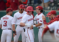 Arkansas right fielder Cayden Wallace is congratulated at the dugout entrance Tuesday, April 6, 2021, by teammates after hitting a solo home run during the first inning of play against UALR at Baum-Walker Stadium in Fayetteville. Visit nwaonline.com/210407Daily/ for today's photo gallery. <br /> (NWA Democrat-Gazette/Andy Shupe)