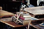Tattered schoolbooks rest on old fashioned school desk