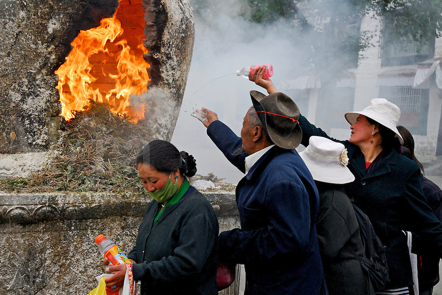 Tibetan Buddhist pilgrims offer water and barley flour at an incense burner on the Barkhor circuit around the Jokhang Temple during Saga Dawa festival, Lhasa, Tibet.