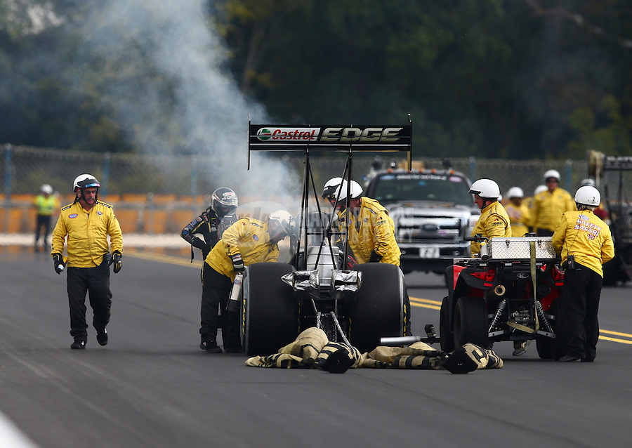 Sep 15, 2013; Charlotte, NC, USA; Safety Safari members come to the aid of NHRA top fuel dragster driver Brittany Force during the Carolina Nationals at zMax Dragway. Mandatory Credit: Mark J. Rebilas-