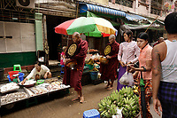 Monks and novices collecting alms in<br /> Yangon, Myanmar, on a sunny day of July 2017<br /> <br /> Those in pink  and light salmon are females