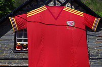 """Pictured: Lynne Humphreys-McCrickett (L) with husband John McCrickett by the 8m x 5m Wales football shirt in Dinas Mawddwy, Gwynedd, north Wales, UK.<br /> Re: Lynne Humphreys-McCrickett has created a 8m x 5m football shirt and displaying it on the side of her house at Minllyn in Dinas Mawddwy, Gwynedd, north Wales, UK.<br /> She said: """"We originally created it in 2016 because there were not any fan zones in north Wales, there certainly weren't any where we are,"""" Lynne said. """"Our neighbour is a football fan too so we were like we will make our own fan zone.""""<br /> Lynne, 50, and her husband John McCrickett, 54, are massive football fans and set about creating the shirt together, which they have dubbed 'Y Crys Mawr Coch', meaning the big red shirt.<br /> Having trained as a seamstress with Laura Ashley when she was just 16, studied at London College of Fashion and having worked as a pattern cutter in London for 20 years, she certainly has the skills for it."""