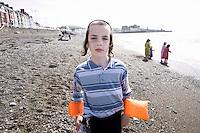 An Hasidic boy wears arm bands on the beach in Aberystwyth.