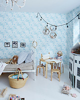 """The little girl's dreamy bedroom features """"Lou's Garden"""" wallpaper and a dollhouse. An Anrey table and stools comprise the crafting corner."""