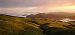 Sunrise over coastal Coromandel Peninsula with farmland in the foreground. New Zealand