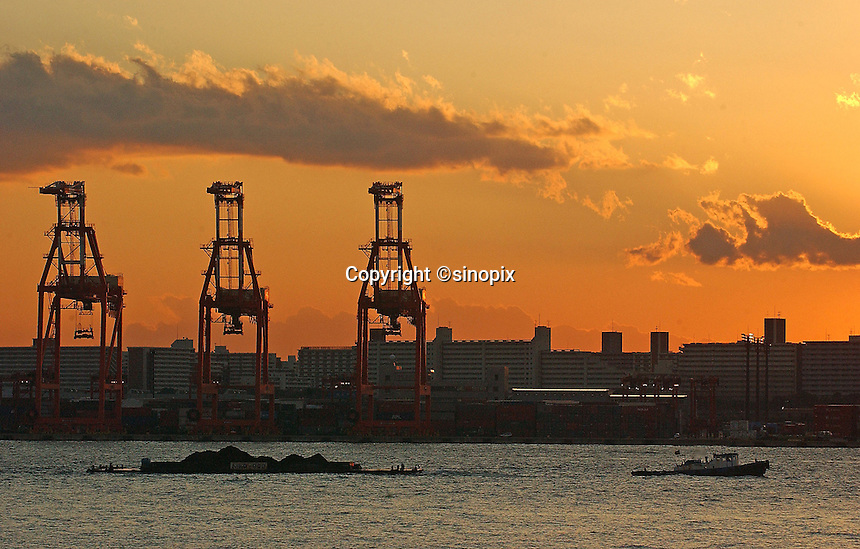 The sun sets over the cranes at container yard of Tokyo Bay, Tokyo, Japan..11 Jan 2005
