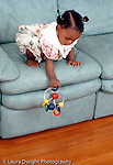 10 month old baby girl leaning over to drop toy off couch African American vertical