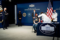 President Joe Biden looks on as a nurse gives a vaccine to Victoria Legerwood Rivera, an Attendance Counselor at Stoddert Elementary School in Northwest DC, as he participates in an event commemorating the 50 million COVID-19 vaccine shot during a ceremony at the White House, Thursday, Feb. 25, 2021. <br /> Credit: Doug Mills / Pool via CNP /MediaPunch