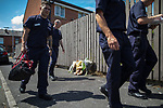 © Joel Goodman - 07973 332324 . 09/07/2017 . Bolton , UK . Firefighters walk by flowers and a teddy bear left opposite the scene on Rosamond Street in Daubhill , where a fatal house fire burned through a mid-terrace house yesterday morning (Saturday 8th July 2017) . Anisha Umerji (40) her two sons Hammad (12) and Yusuf (ten) and her daughter Khadija (five) all died in the blaze. Their father Zubair (Anisha's husband) remains in hospital . Photo credit : Joel Goodman