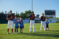 Batavia Muckdogs outfielders Mathew Brooks (46), Thomas Jones (49), and Jhonny Santos (13) stand for the national anthem with young fans before a game against the Auburn Doubledays on July 4, 2017 at Dwyer Stadium in Batavia, New York.  Batavia defeated Auburn 3-2.  (Mike Janes/Four Seam Images)