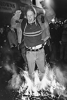 A man jumps into a tar barrel fire. Tar barrels are set alight and run through the market square as part of a 17th Century tradition held around the 5th November - Guy Fawkes night - and believed to ward off evil spirits in Ottery St. Mary, Devon.