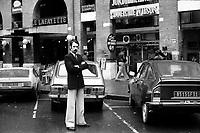 """""""Portai [Portay], Picard, Me Cathala, Me Bouscatel, Me Rastoul"""". Place Wilson. 30 novembre 1976. Vue d'ensemble de face de Christian Portay (un des accusés) ; en arrière-plan entrée du restaurant """"Le Lafayette"""", voitures stationnées. Cliché pris le jour d'une reconstitution judiciaire dans le cadre de l'affaire du meurtre de René Trouvé. Observation: Affaire René Trouvé-Birague : le 19 février 1976, le journaliste René Trouvé est assassiné d'une balle dans la tête, par deux inconnus, alors qu'il regagne son domicile au 33 rue Bayard."""