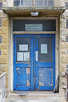 Pictured: One of the entrances of the old Police Station in Aberystwyth, Wales, UK. Wednesday 28 August 2019<br /> Re: Opened 1866, built by the Hafod Hotel Co as the Queens Hotel; architects, Hayward and Davies; builder George Lumley of Aberystwyth. Sold in 1877 and later converted to local government use; remodelled in1950 by G R Bruce, County Architect.<br /> Detached towards N end of the Promenade, with main entrance to side elevation in Albert Place and rear elevation to Queens Road.<br /> Hotel de Ville style. Asymmetrical 3-storey attic and basement snecked rubble 13-bay W (Promenade) elevation; stepped front with mostly vermiculated dressings, stock brick voussoirs, deep entablature and cornice and cill bands; buttresses to ground floor centre. Steep pitch mansard slate roof with truncated chimney stacks. Dormers with steep overhanging roofs and casement windows; paired to left. 3-bays advanced near the right hand end and with additional storey and splayed angles to 2nd floor (with small cast-iron parapets) and 3rd floor; also to top floor) with small cast-iron parapets) and 3rd floor; also to top floor at the corner. Sash windows, some paired; anthemion panelled cast-iron window box holder across central bays.
