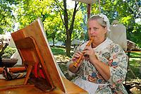 Wife of British redcoat plays an English soprano flute at a Revolutionary War encampment, Fort Ticonderoga, New York, USA.