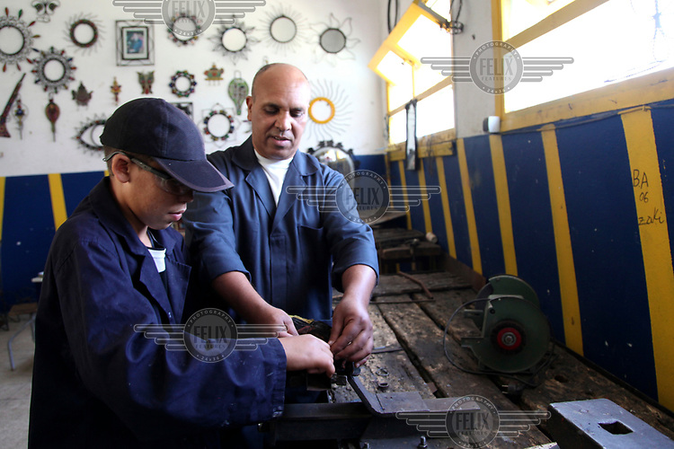 A 15 year old boy is taught metal work at the Centre de Protection d'Enfance for youths who have been in trouble with the law.