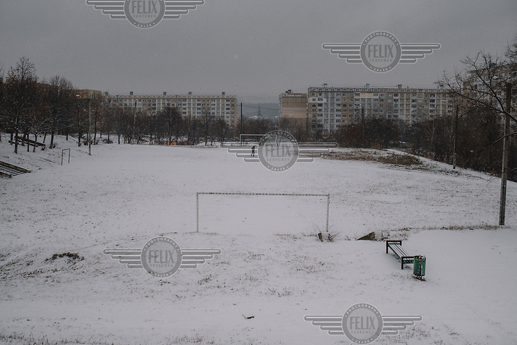 A man walks across a snow covered a football pitch in the Ciocana district.