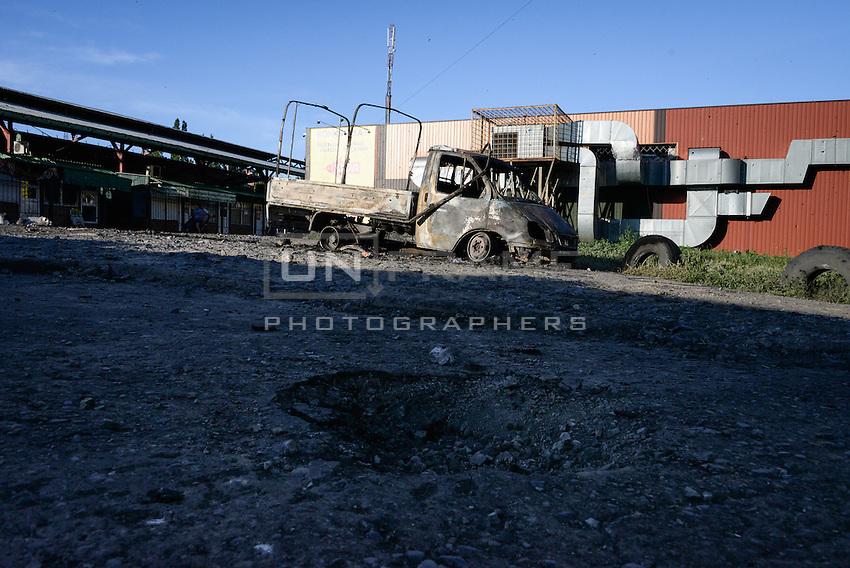 A hole and a burned van after shelling on the street of Slovyansk. Ukraine.