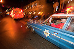 Chief Scott Morrison drives Jackson Police Department's vintage 1960s Ford police car Sutter Creek's annual Parade of Lights Christmas parade downtown on a rainy night in the  Mother Lode of Calif.