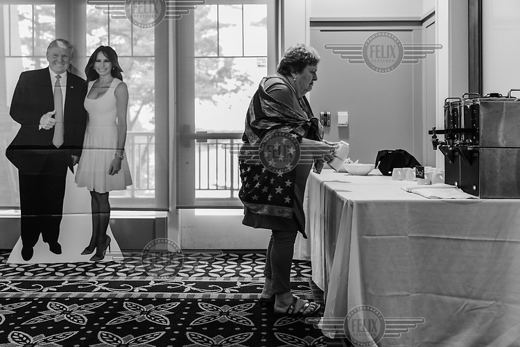 An attendee at a 'Women for Trump' election campaign event, held at a country club, gets herself coffee ar a table beside cardboard cut out figures of Donald and Melania Trump.