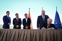 Pictured: Matthew Nimetz of the United Nations (R) signs the deal while looked on by (L-R) Nikola Dimitrov Minister of Foreign Affairs of FYROM, Zoran Zaevat, Prime Minister for FYROM, Greek Prime Minister Alexis Tsipras (R), Greek foreign minister Nikos Kotzias at Prespa Lake in northern Greece. Sunday 17 June 2018<br /> Re: Greece and the Former Yugoslav Republic Of Macedonia (FYROM) have signed a deal that aims to settle a decades-long dispute over the country's name.<br /> Under the agreement, Greece's neighbour will be known as North Macedonia.<br /> Heated rows over Macedonia's name have been going on since the break-up of the former Yugoslavia, of which it was a part, and have held up Macedonia's entry to Nato and the EU.<br /> Greece has long argued that by using the name Macedonia, its neighbour was implying it had a claim on the northern Greek province also called Macedonia.<br /> The two countries' leaders, Mr Tsipras and his Macedonian counterpart Zoran Zaev announced the deal on Tuesday and have pressed ahead despite protests.<br /> The two countries' foreign ministers signed the deal on Lake Prespa on Greece's northern border on Sunday.<br /> The agreement still needs to be approved by both parliaments and by a referendum in Macedonia.