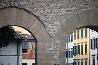 Firenze: A part of an old painting on a wall, and the windows of typical buildings, between two old arcs, just outside the historical center.