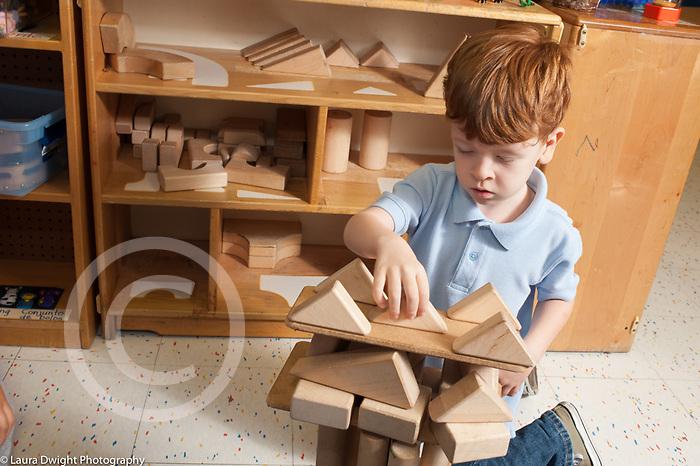 Education preschool 3-4 year olds boy placing triangle blocks balanced on board on top of wooden block construction