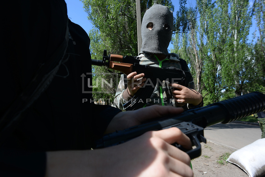 Children play war games mimicking the outfit and the equipment (toy guns) of the Pro-Russian forces nearby one of their outpost. Near Slavyansk, Ukraine. May 6, 2014