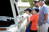 Kaleb Fuqua, 9, (bottom right) lifts Dallas Fuqua, 7, so he can look into the driver's side of an antique car also shown with Brent and Randy Fuqua (top), Saturday, July 24, 2021 during a farmer's market at Harry Sbanotto Park in Tontitown. The Towntitown Farmer's Market hosted an antique car show and customs exhibit in addition to their regular farmer's market. Check out nwaonline.com/210725Daily/ for today's photo gallery. <br /> (NWA Democrat-Gazette/Charlie Kaijo)