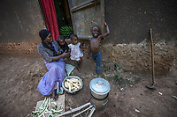 Uganda, Angi. Nabiirah SserKumba (29) and her husband Hakim have seven children. She uses the BioLite stove as it's faster and emits less smoke. It also charges a light, portable radio and her mobile phone. Cooking with her children, Jawadah her son (5), Nasejje her daughter (3).