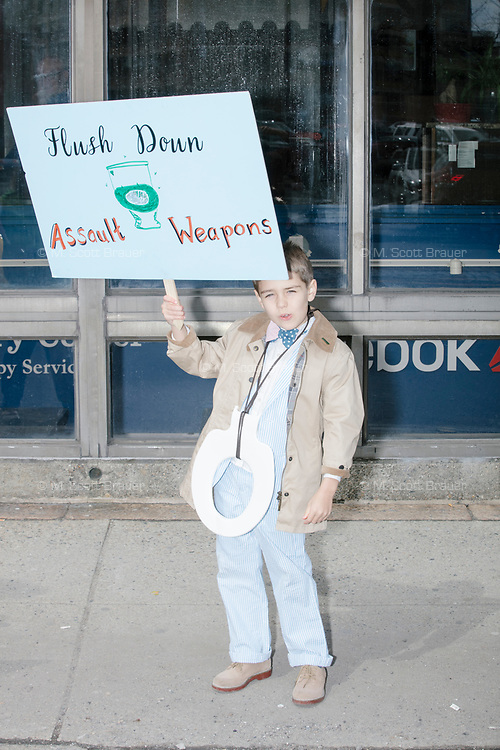 """Ronan, age 7, holds a sign reading """"Flush down assault weapons,"""" as he takes part in the March For Our Lives protest, walking from Roxbury Crossing to Boston Common, in Boston, Massachusetts, USA, on Sat., March 24, 2018, in response to recent school gun violence."""